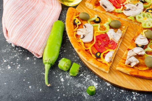 暗い机の上で新鮮なトマトと赤いトマトグリーンオリーブキノコとおいしいキノコのピザを閉じるトップビューピザ生地イタリアの肉料理