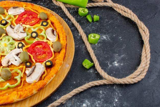 灰色の机の上に赤いトマトオリーブキノコとフレッシュトマトとキノコのおいしいキノコピザ
