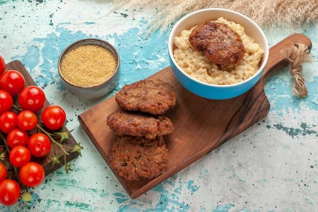 Vista ravvicinata gustoso porridge con cotolette di carne e pomodorini sulla scrivania blu