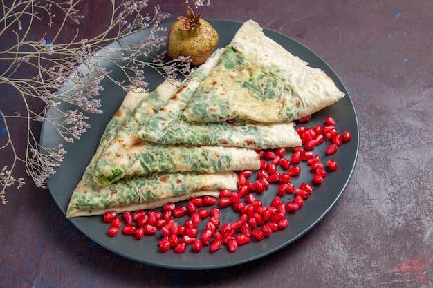 Vista ravvicinata dall'alto gustose qutabs con verdure all'interno su superficie scura pasto grasso piatto da cucina impasto