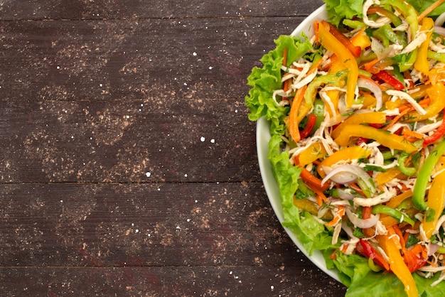 Вид сверху овощной салат с нарезанными овощами и зеленым салатом внутри круглой тарелки на коричневом, овощном салате