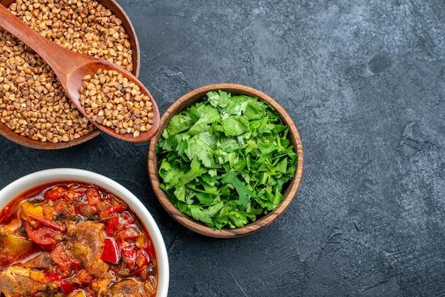 Vista dall'alto ravvicinata gustosa zuppa di verdure con grano saraceno crudo su spazio grigio