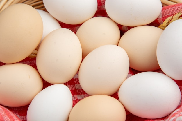 Top close view white chicken eggs inside basket with towel