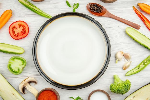 Vista ravvicinata dall'alto piatto rotondo bianco tagliato verdure spezie in ciotole cucchiaio di legno su sfondo bianco