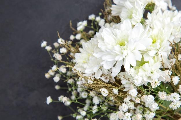 Вид сверху крупным планом белые свадебные цветы на темном фоне