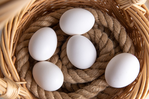 Top close view white whole eggs inside basket on the white desk.