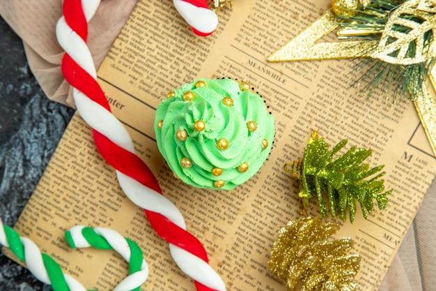 Vista ravvicinata dall'alto albero di natale cupcake caramelle di natale ornamenti di natale sul giornale scialle beige su sfondo scuro