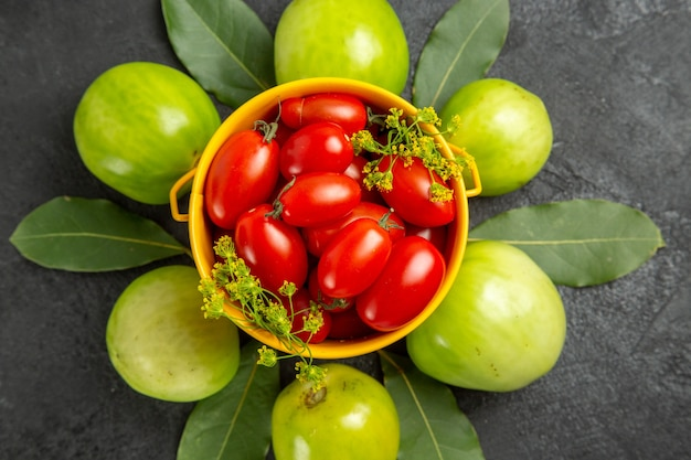Top close view yellow bucket filled with cherry tomatoes and dill flowers surrounded with green tomatoes on dark background