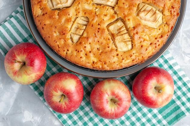 Top vista ravvicinata yummy torta di mele dolce al forno all'interno della padella con le mele sulla scrivania bianca torta torta biscotto zucchero dolce cuocere