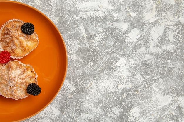 Torte gustose di pasta vista ravvicinata con zucchero in polvere all'interno della piastra sulla superficie bianca