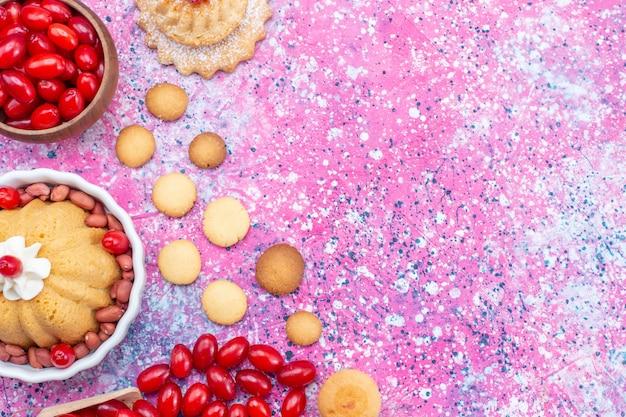 Вид сверху вкусный простой торт со сливками и свежим арахисом с красным кизилом на ярком светлом столе