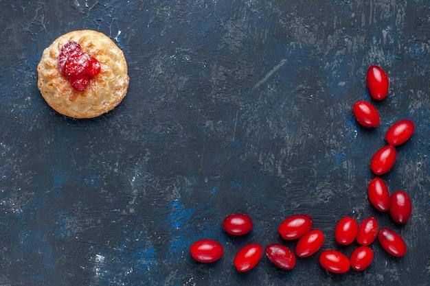 Torta dolce gustosa vista ravvicinata con cornioli rossi su sfondo grigio scuro