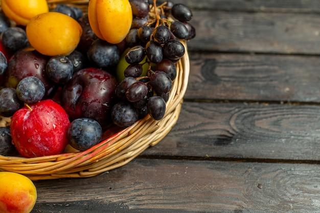 Корзина со спелыми и кислыми фруктами, такими как виноград, абрикосы, сливы, на коричневом столе.