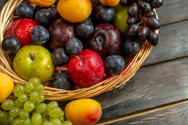 Корзина с фруктовыми спелыми и кислыми фруктами, такими как виноград, абрикосы, сливы, на коричневом деревенском столе.