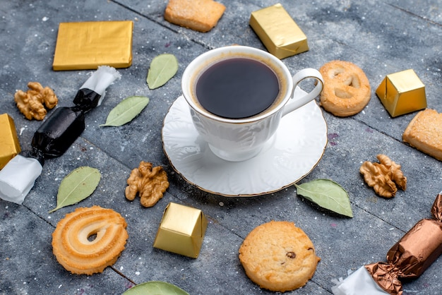 Top closer view of cup of coffee with cookies walnuts on grey