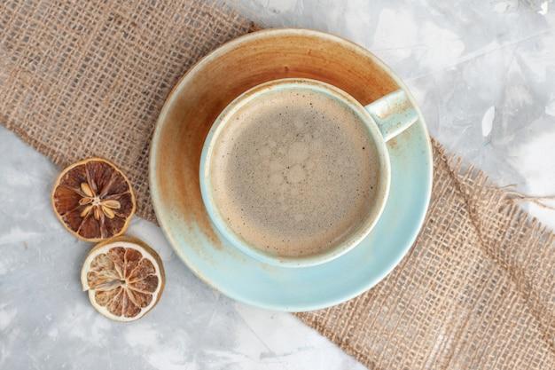 Top vista ravvicinata tazza di caffè con latte all'interno della tazza sulla scrivania bianca bere caffè latte espresso americano