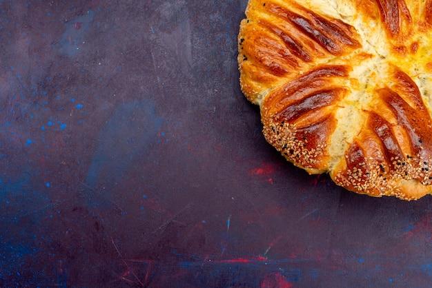 Top più vicino vista deliziosa pasticceria panino al forno su sfondo scuro.