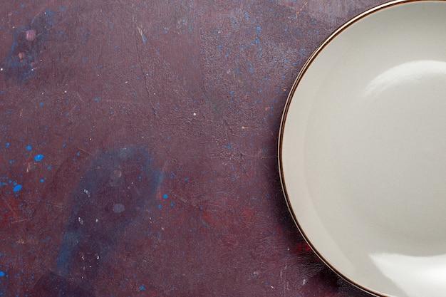 Vista più ravvicinata dall'alto piatto rotondo vuoto fatto di lastra grigia sulla foto a colori delle posate di vetro della lastra di superficie scura