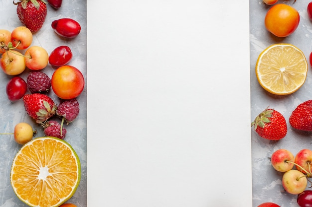 Top vista più ravvicinata frutta fresca limoni e ciliegie con blocco note sul pavimento bianco frutta matura fresca pastosa