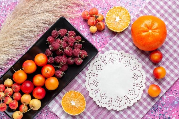 Vista più ravvicinata dall'alto di lamponi e prugne di frutta fresca all'interno della forma nera sulla superficie rosa