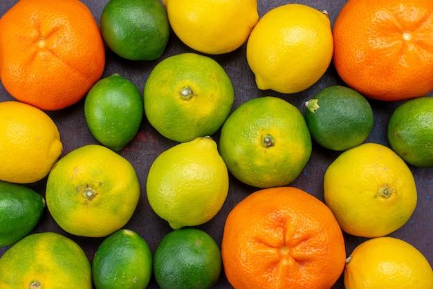 暗い机の上で他の柑橘類で着色された新鮮なジューシーなみかんオレンジを上から見る柑橘類の熱帯のエキゾチックなオレンジ色の果実