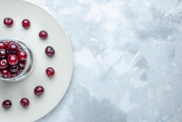 Vista superiore più ravvicinata di ciliegie acide fresche all'interno della piastra sulla scrivania bianca frutta bacche acide vitamina estate