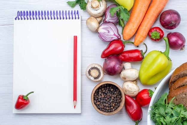 Vista ravvicinata dall'alto di verdure fresche come cipolle carote pepe con pane sulla scrivania leggera