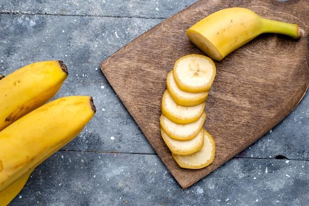 Vista più ravvicinata dall'alto di banane gialle fresche affettate e intere su grigio
