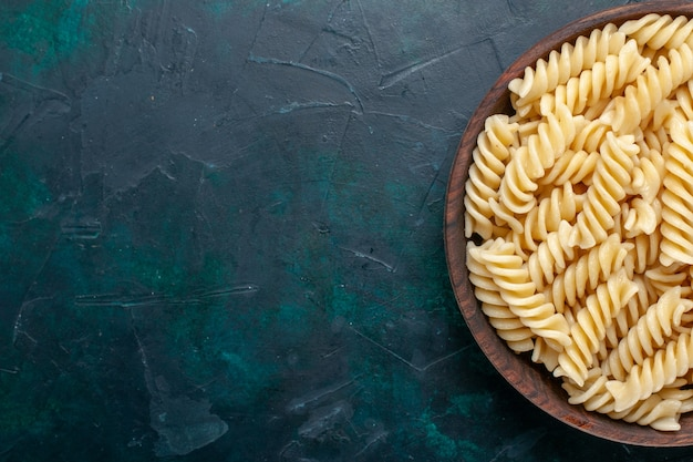진한 파란색 책상에 갈색 냄비 안에 맛있는 이탈리아 파스타를 가까이에서 볼 수 있습니다.