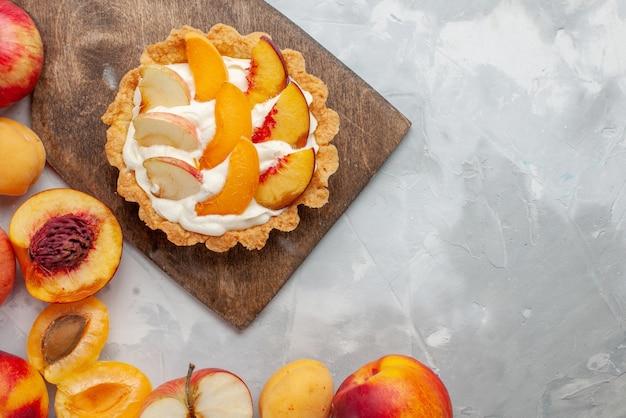 Vista ravvicinata dall'alto della piccola torta cremosa con frutta a fette e crema bianca insieme a frutta fresca sulla scrivania bianco chiaro