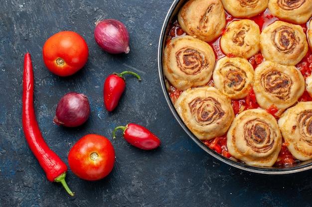 Вид сверху на вкусное тесто, мясо внутри сковороды вместе со свежими овощами, такими как лук, помидоры, перец на темноте