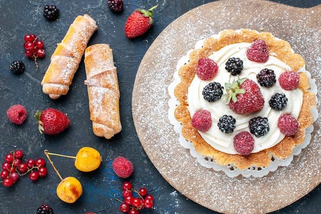 Вид сверху на вкусный маленький торт с сахарной пудрой и ягодами вместе с браслетами на темном столе