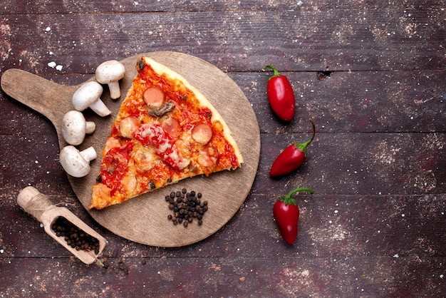 Вид сверху на вкусный кусок пиццы со свежими грибами, помидорами, красным перцем на коричневом столе