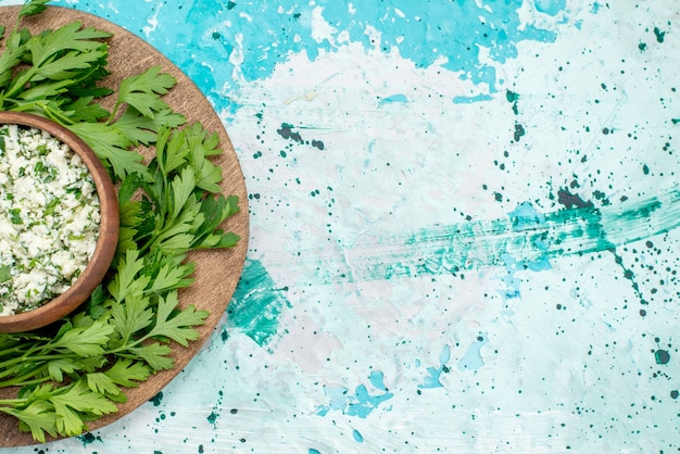明るい青の茶色のボウルの中に緑と新鮮なスライスしたキャベツのサラダの上面拡大図