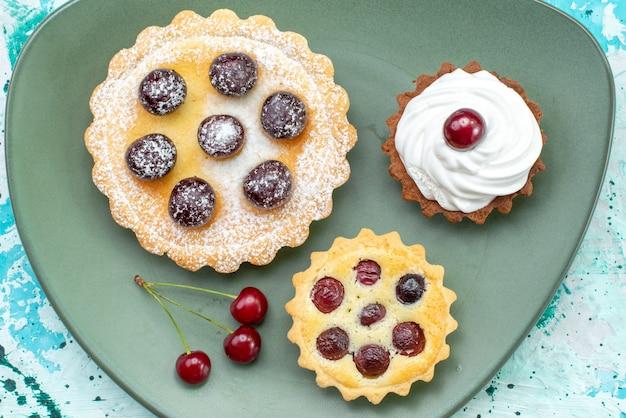 Вид сверху на маленькие пирожные с сахарной пудрой, фруктовый крем на голубом