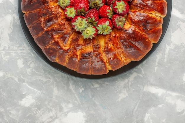 Вид сверху на вкусный клубничный пирог со свежей красной клубникой