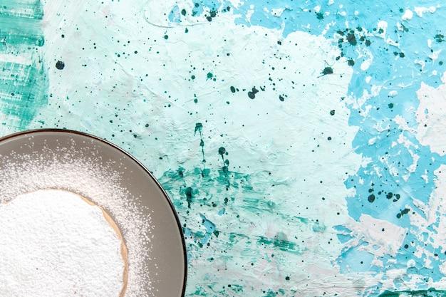 Torta rotonda vista dall'alto più ravvicinata con zucchero in polvere all'interno del piatto sulla superficie azzurra torta cuocere biscotti zucchero colore tè dolce