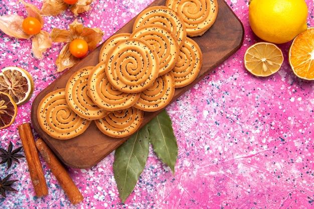 ピンクの机の上にシナモンとレモンが並ぶ甘い小さなクッキーの周りの上部の拡大図。