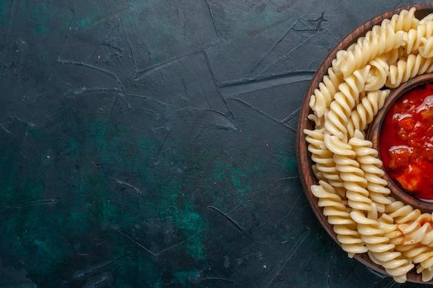 Pasta italiana a forma di vista dall'alto più ravvicinata con salsa di pomodoro su superficie blu scuro