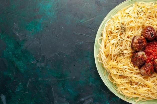 Vista ravvicinata dall'alto gustosa pasta italiana con polpette di carne sulla superficie blu scuro