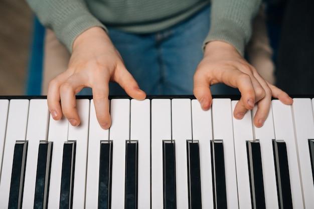 피아노 치는 법을 모르는 알아볼 수 없는 어린 소년의 손을 가장 가까이에서 본 모습