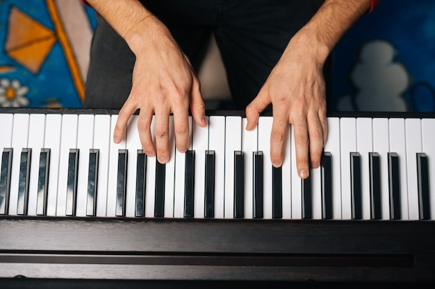 음악 교육의 가정 개념에서 피아노를 연주하는 알아볼 수 없는 남자의 손에 대한 상위 근접 촬영 보기