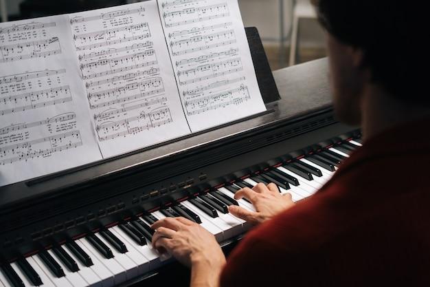 집에서 피아노를 연주하는 알아볼 수 없는 음악가 남자의 손을 가장 가까이에서 볼 수 있습니다.