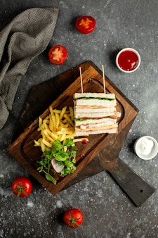 Top  club sandwich with vegetables french fries and sauces on wooden broad