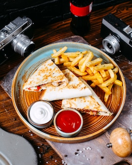 Top  clubsandwich with french fries and sauces on wooden table