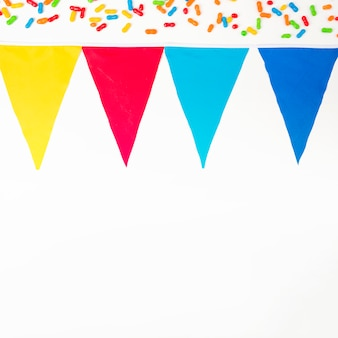 Top colorful marmalade candies and bunting flag on white backdrop