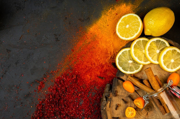 Top  colorful spices with lemon slices kumquats and cinnamon sticks on black
