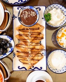 Верхние блинчики с шоколадным кремом и орехами на блюде