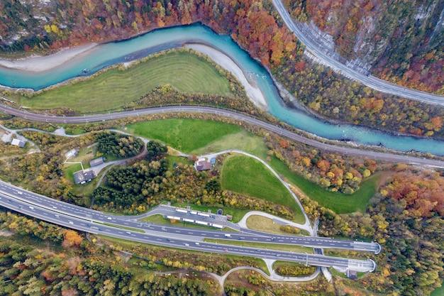 地下のトンネルから出て行く高速道路の高速道路の夜明けの航空写真