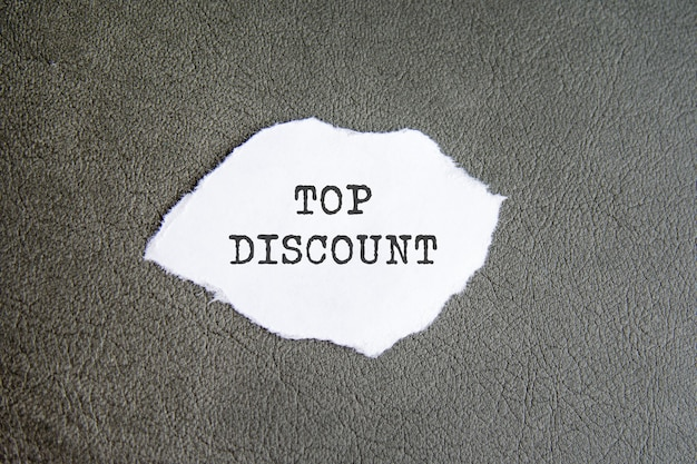 Top discount sign on the torn paper on the grey background.